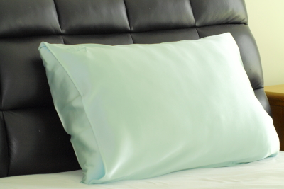 mint silk pillow on bed bed with black headboard